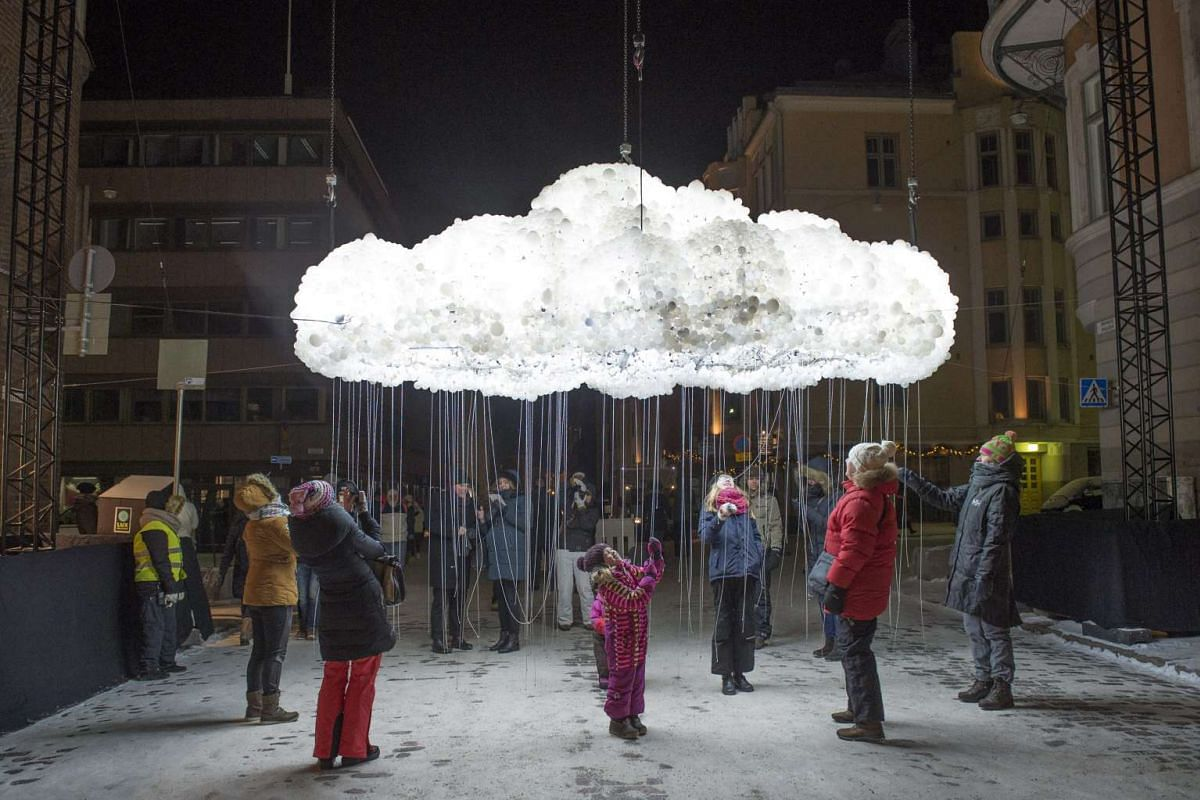 People examining the interactive sculpture, Cloud, by Canadian artists Caitlind r.c. Brown and Wayne Garret at the Lux Helsinki light festival, in Helsinki, Finland on Jan 6, 2016.