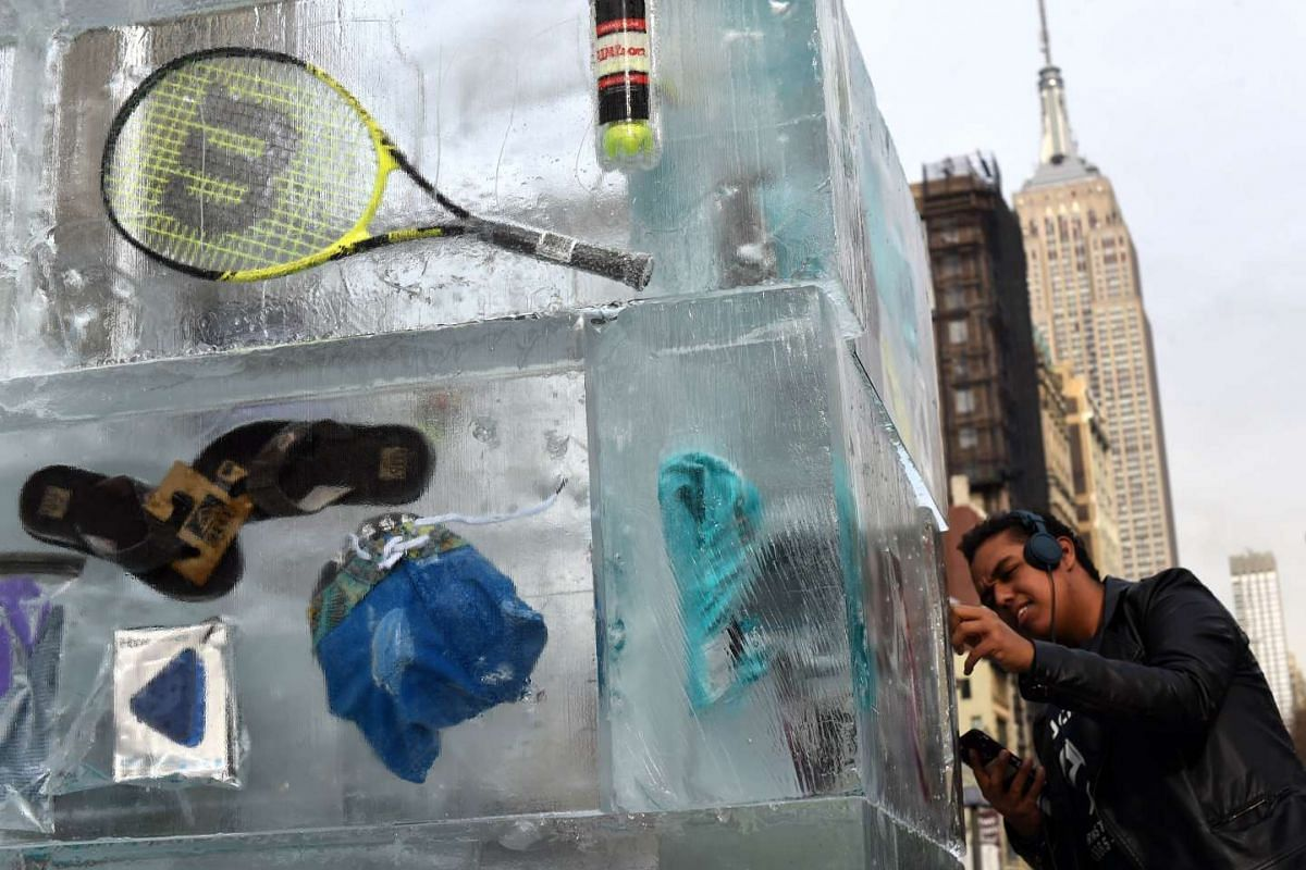 People passing by leisure items frozen in a giant block of ice during a JetBlue Airways event in Madison Square Park in New York on Jan 7, 2016.