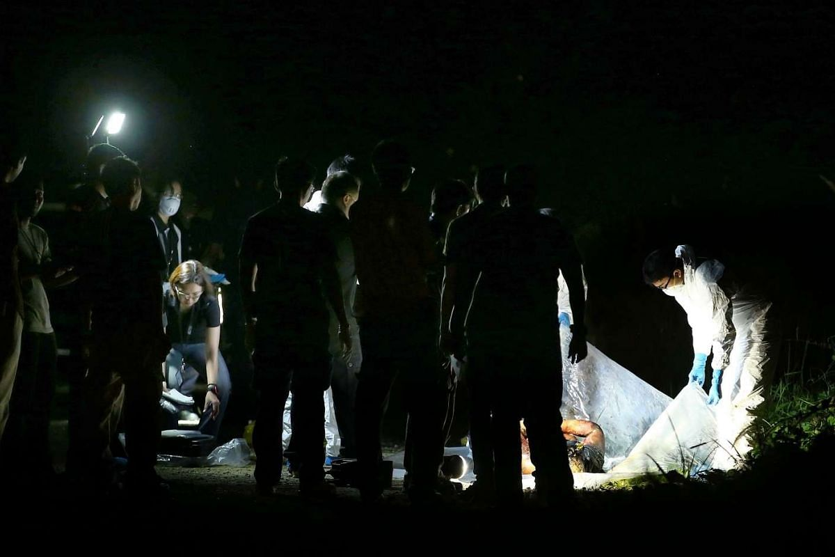 Police investigators with the body of Mr Dexmon Chua in a military training area near Sungei Gudong camp.