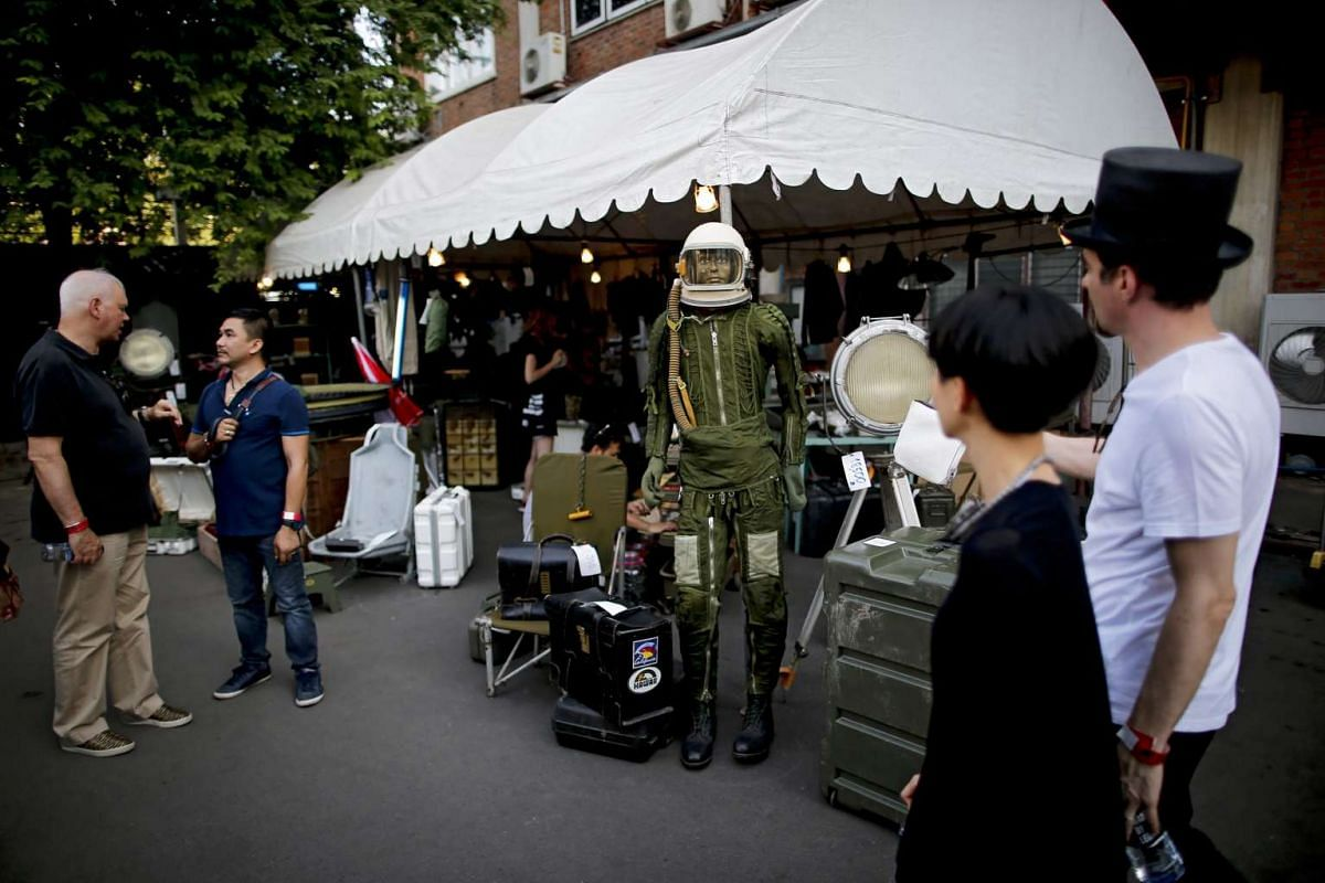 Visitors walking past a mannequin dressed in pilot clothing.