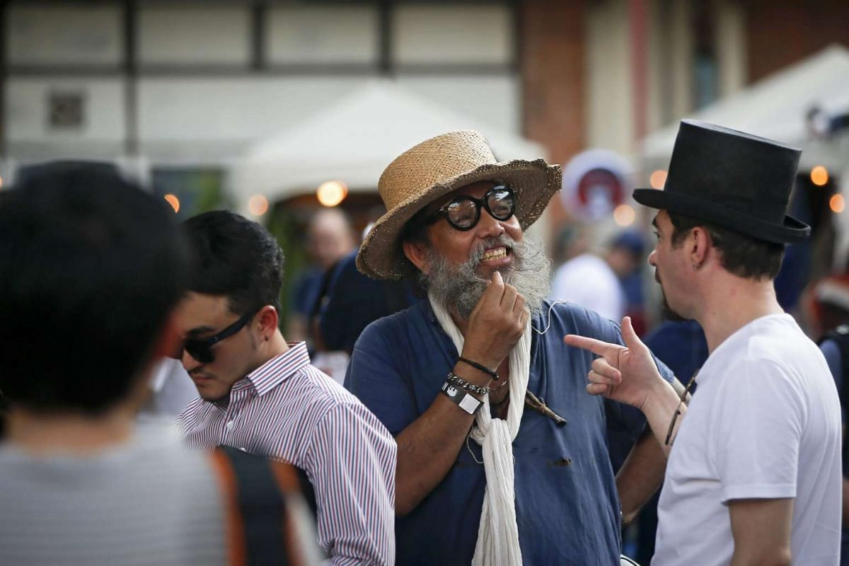 A tourist (right) talking to a local man selling hats at his stall.