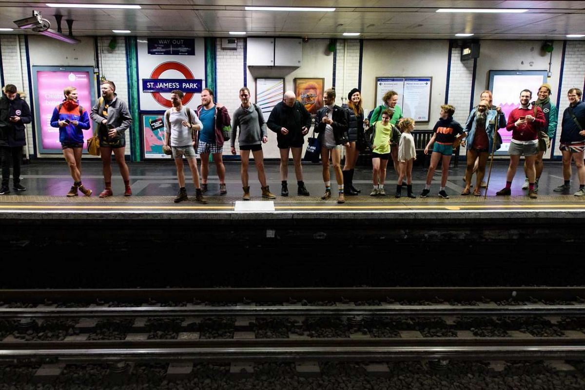 """Participants in the annual International """"No Pants Subway Ride"""" wait at a station for a London underground train in London on Jan 10."""