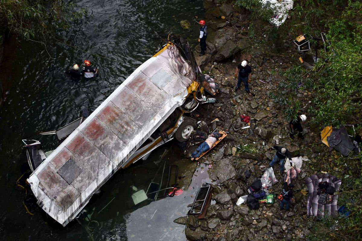 A body lies on a stretcher as rescuers survey the site where a bus ran off a highway bridge in Atoyac, Mexico on Jan 10.