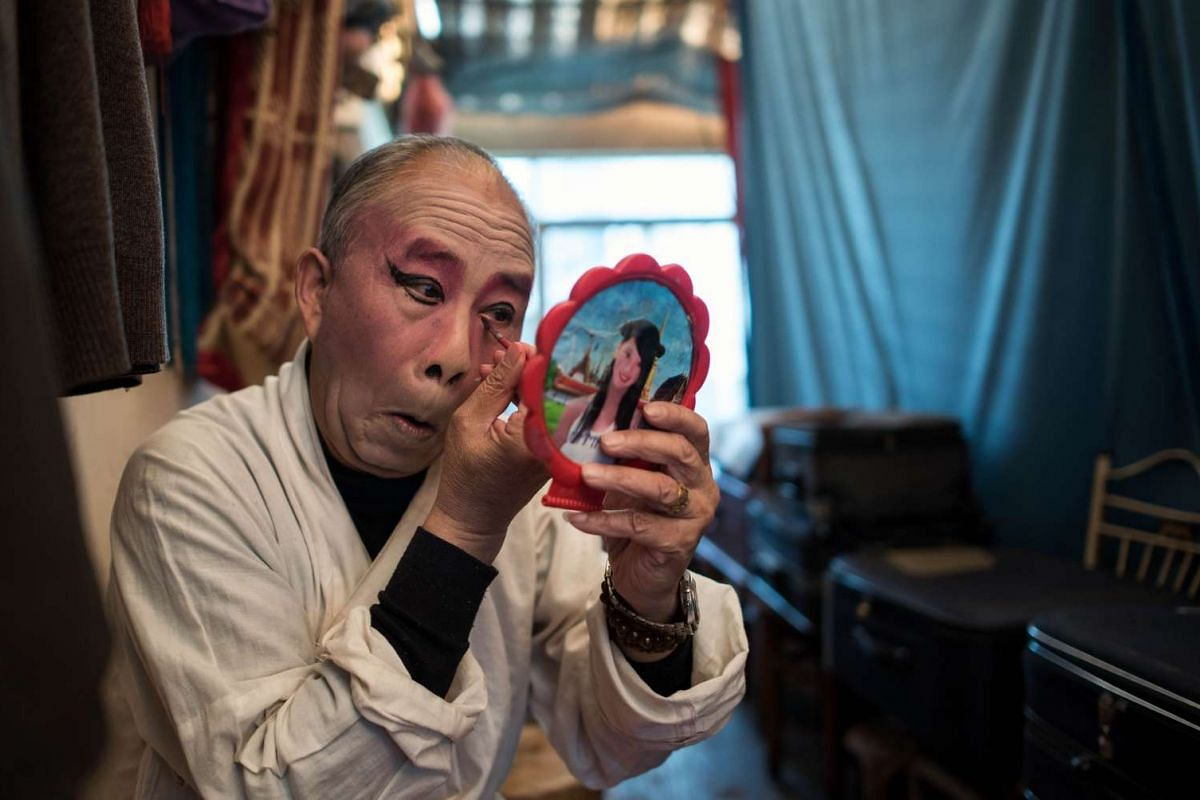 An actor of the 'Flower Lantern' troupe putting on his make up backstage before a show.