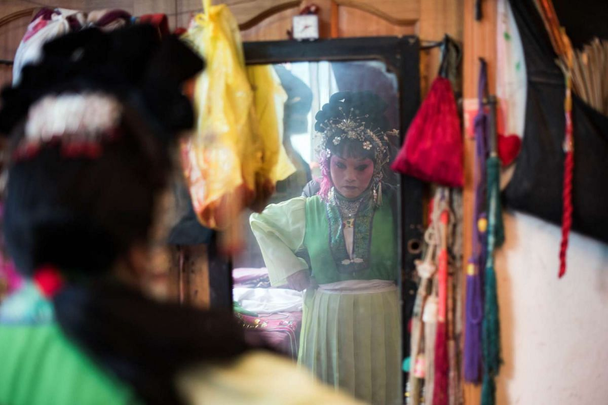 Zhong Huifangi of the 'Flower Lantern' troupe getting dressed during a show.