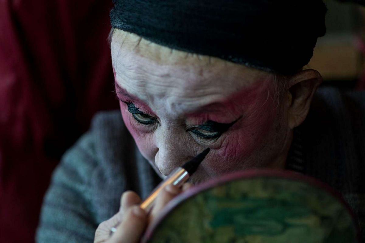 He Zhengcai, director of the 'Flower Lantern' troupe, putting on his makeup backstage before a show.