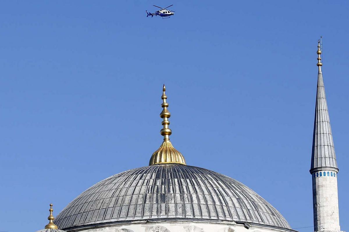 A police helicopter flies over the Ottoman-era Sultanahmet mosque, known as the Blue mosque, following an explosion nearby, in Istanbul, Turkey.