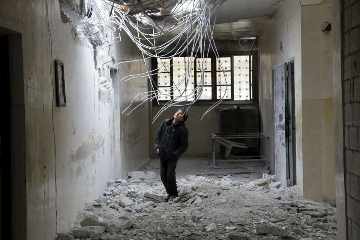 A boy inspects damage inside his school, due to what activists said was an air strike carried out yesterday by the Russian air force in Injara town, Syria.