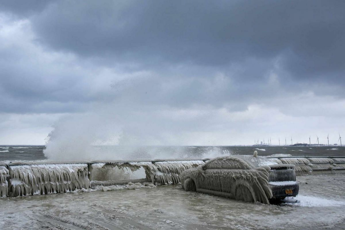 A car covered with ice remains stranded on the waterfront in Hamburg, New York.
