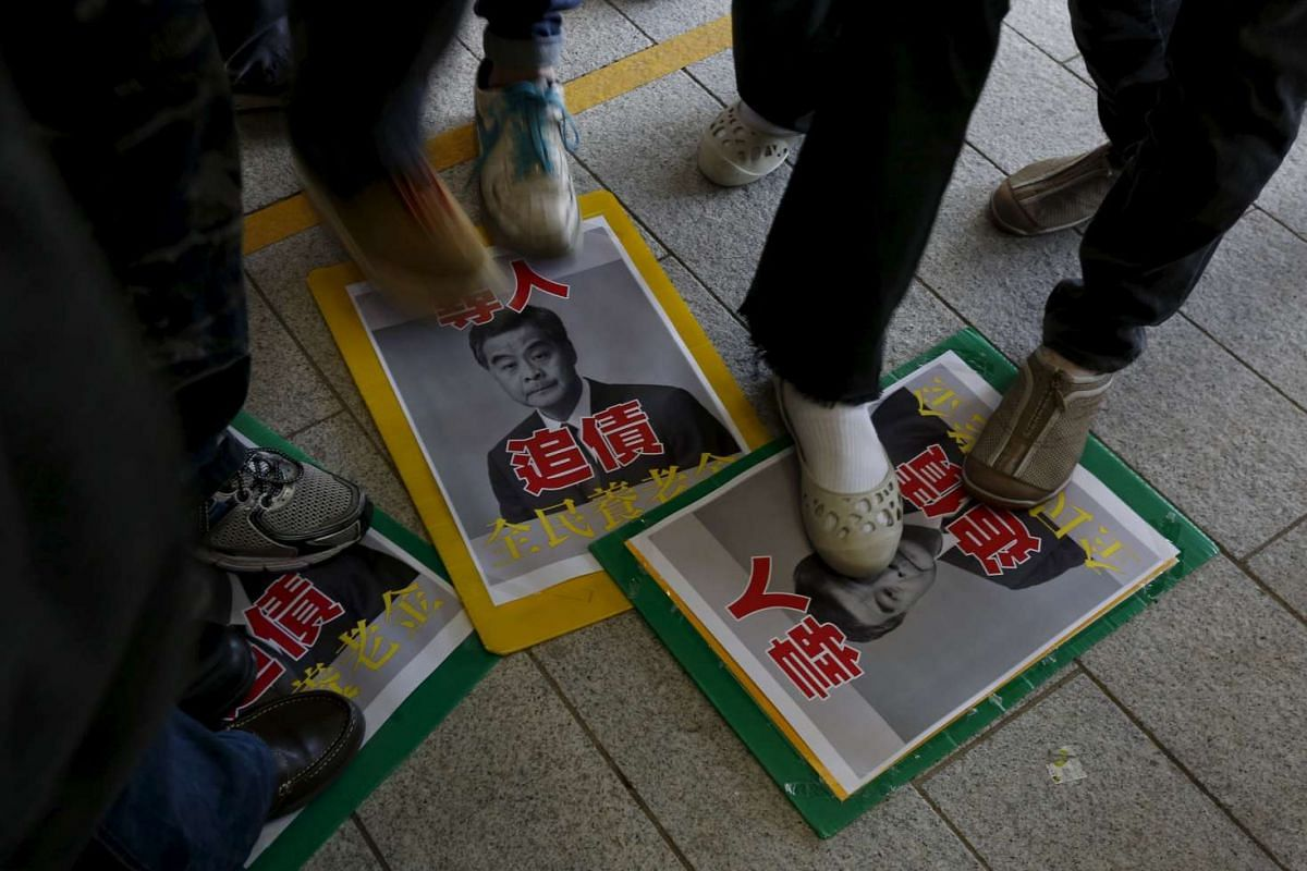 Protesters demanding better social welfare step on the portraits of Hong Kong Chief Executive Leung Chun Ying, before his annual policy speech.