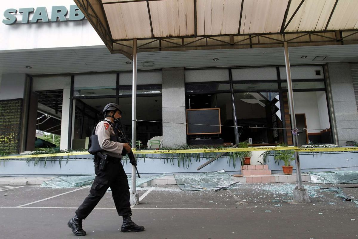10.50 - 10.55am: An Indonesian police officer walks past debris at the scene of a bomb blast at a Starbucks cafe in Jakarta on Jan 14, 2016.