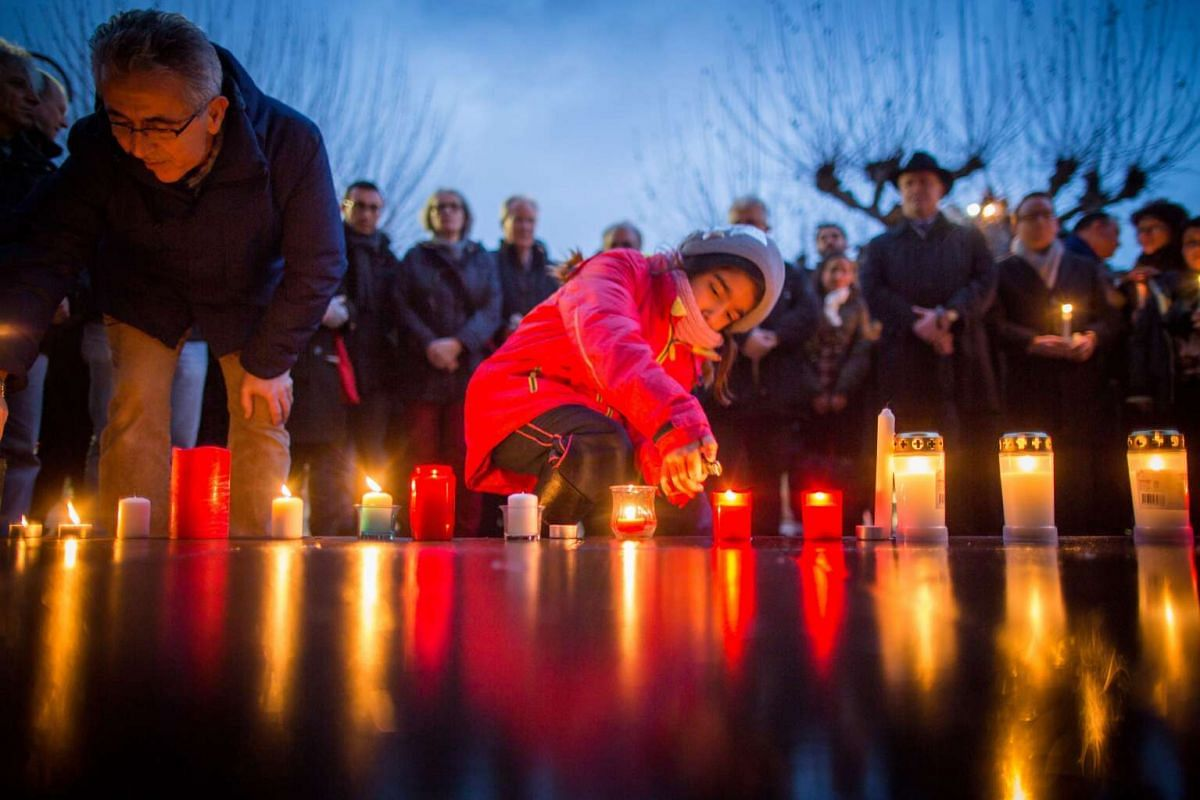 The eight-year old Alina (centre) and the Hessian SPD member of parliament Turgut Yüksel (left) light candles at Paulsplatz during a memorial service for the victims of the terrorist attack in Istanbul on Jan 12, 2016.