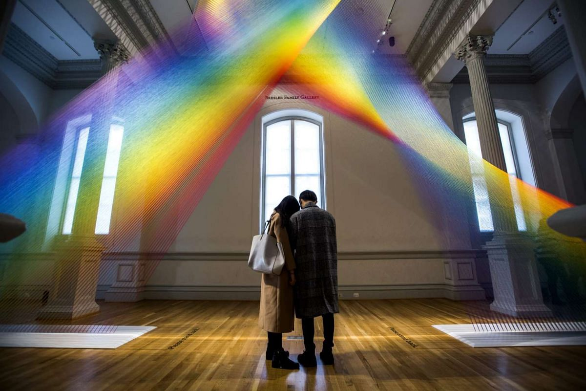 Visitors review their mobile phone photos of an installation called Plexus A1 by artist Gabriel Dawe, displayed at the Wonder exhibit at the Renwick Art Gallery in Washington, DC, United States, on Jan 13, 2016.
