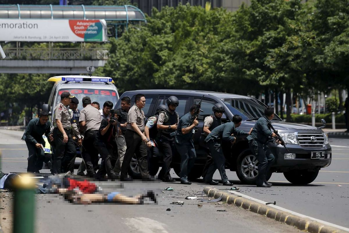 11am: Bodies are seen as Indonesian police hold rifles while walking behind a car for protection in Jakarta on Jan 14, 2016.