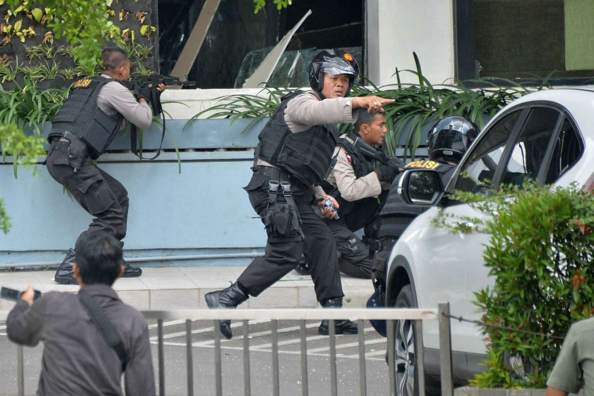 10.50 - 10.55am: Indonesian police take position and aim their weapons as they pursue suspects outside the cafe on Jan 14, 2016.