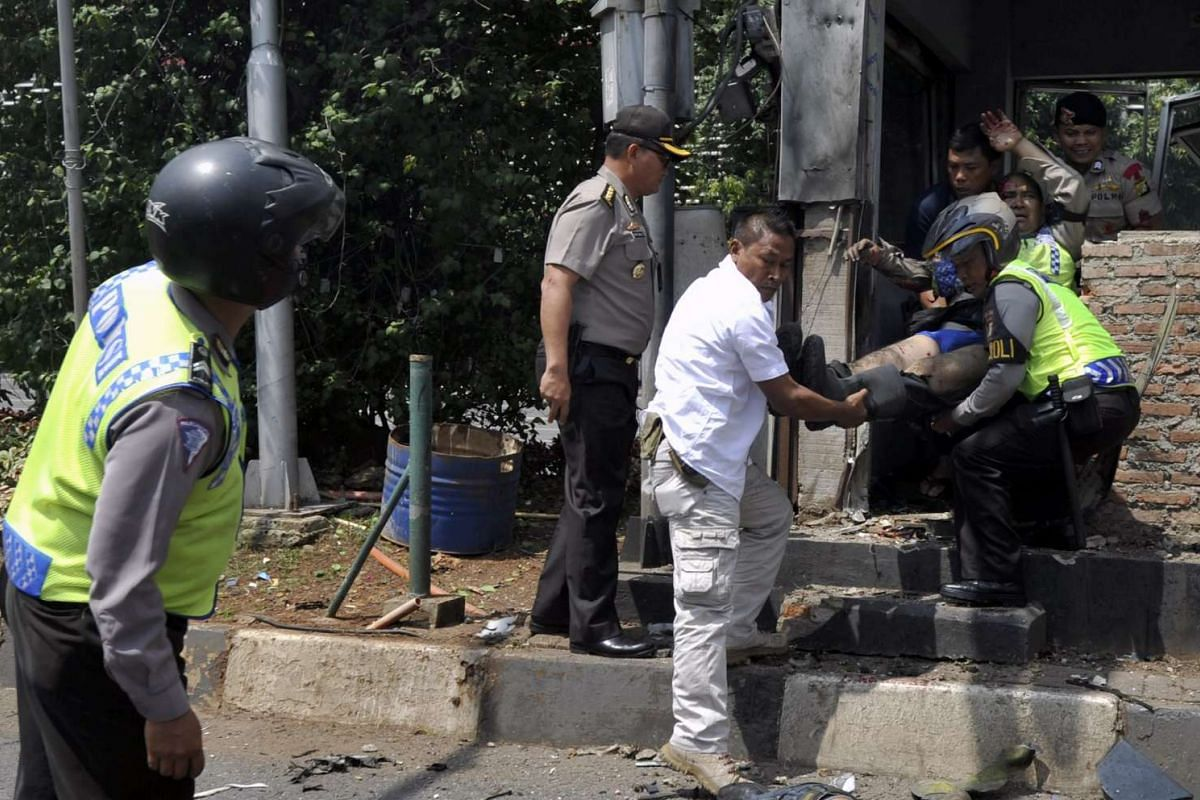 11am: Indonesian police officers evacuating an injured policeman after a bomb blast at a police post in Jakarta on Jan 14, 2016.