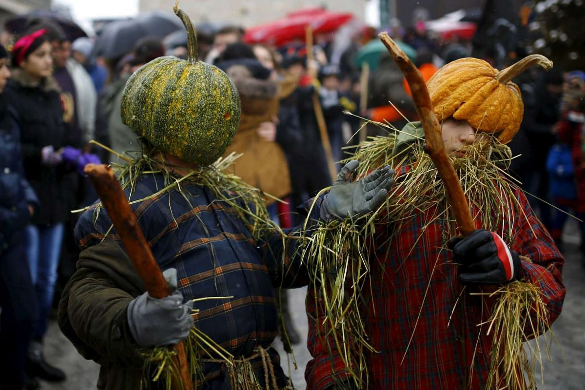 Revellers participate in a parade on the street during a carnival in the village of Vevcani on Jan 13, 2016.