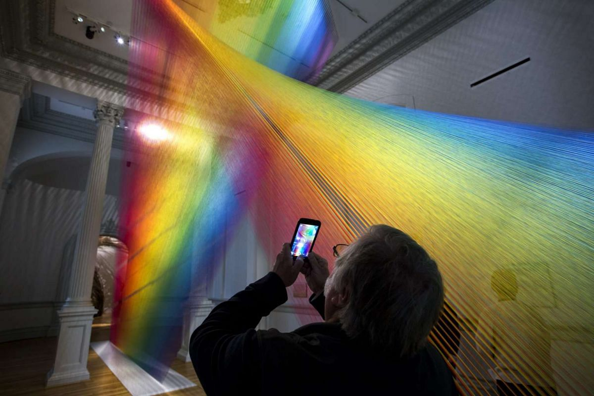 A visitor takes a picture of an installation called Plexus A1 by artist Gabriel Dawe, at the Wonder exhibit displayed at the Renwick Art Gallery in Washington, DC.