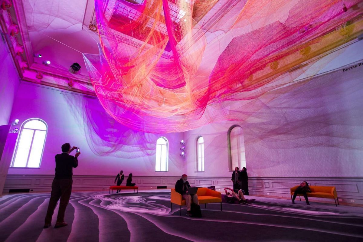 Visitors take in a piece called 1.8 by artist Janet Echelman, at the Wonders exhibit displayed at the Renwick Art Gallery in Washington, DC.