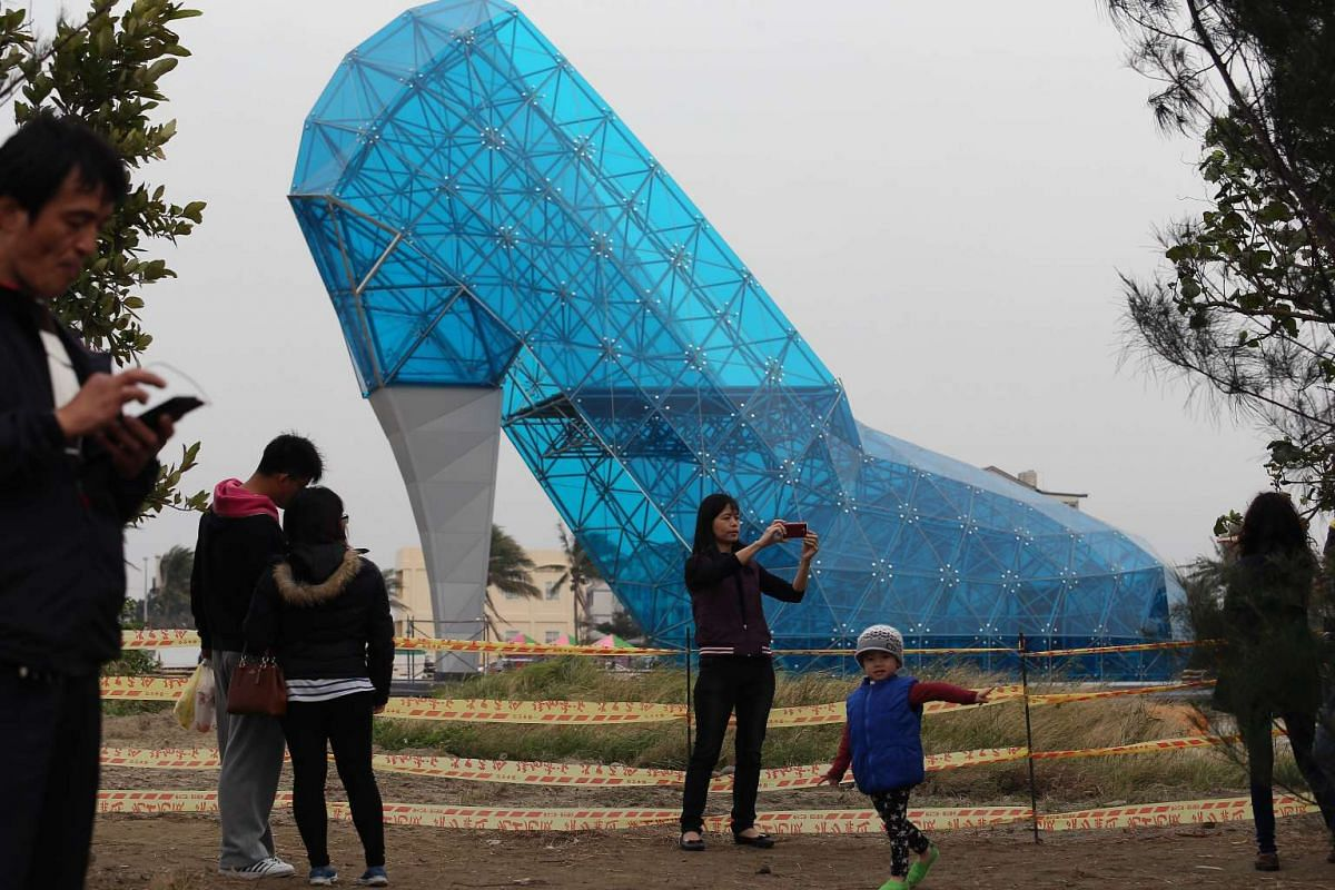 Tourists take pictures in front of a shoe-shaped church in southern Chiayi, Taiwan, on Jan 11, 2016.