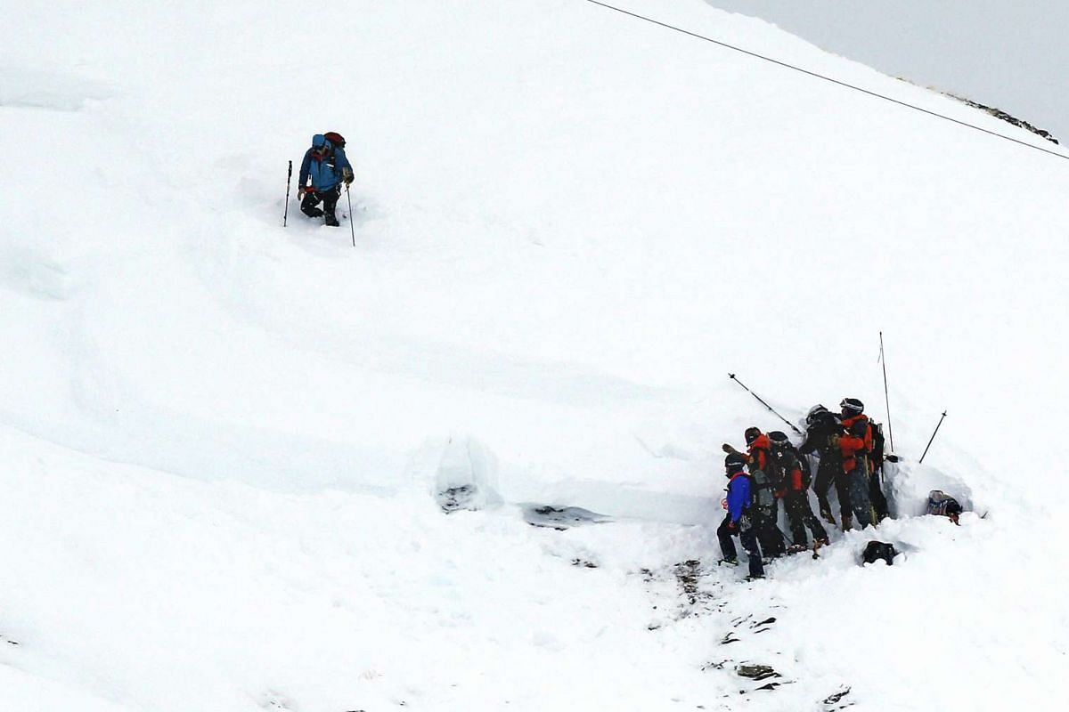 Members of a rescue team search in the snow for missing people after an avalanche swept away a group of people that included a party of schoolchildren, in Les Deux Alpes, France, on Jan 14, 2016.
