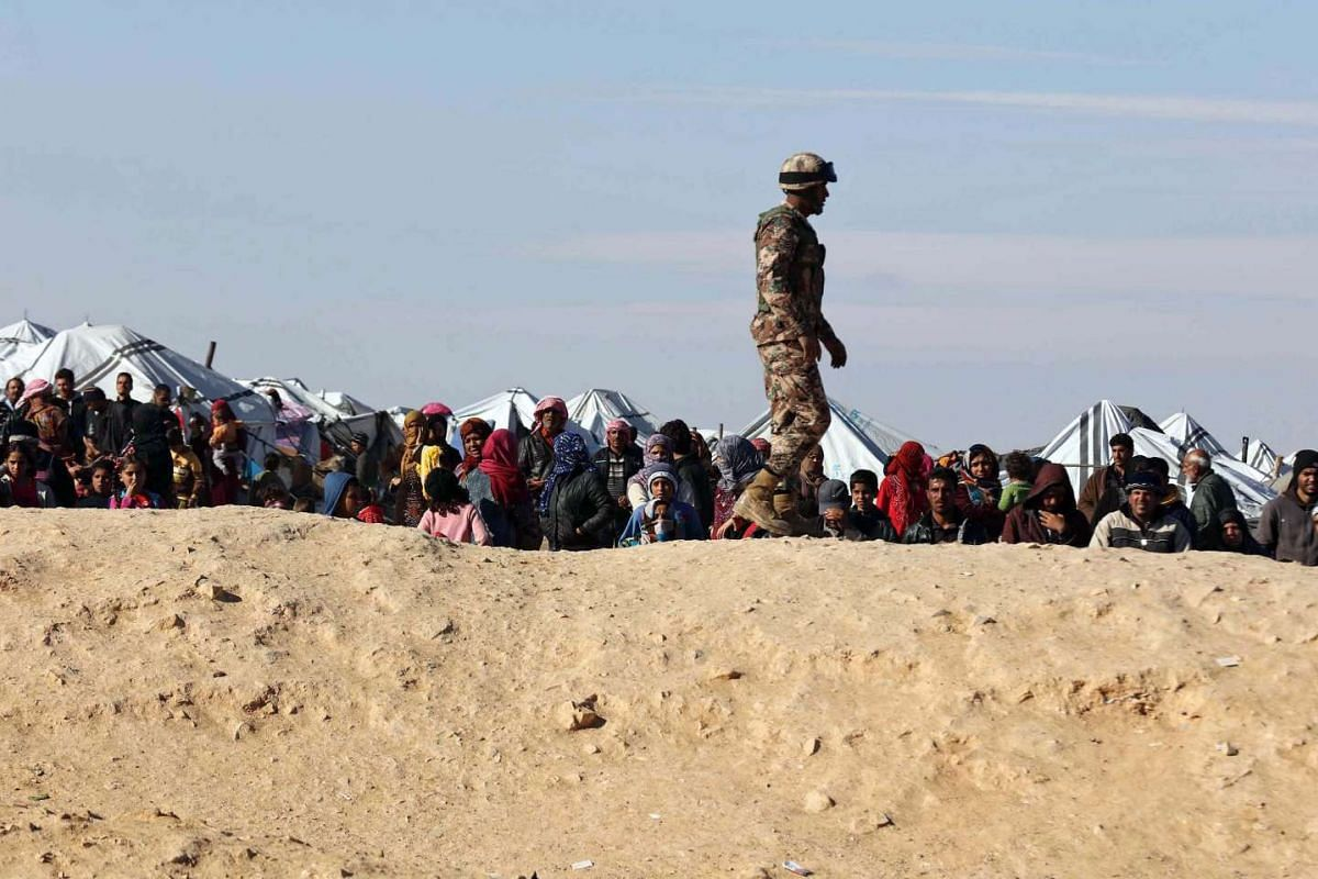Syrian refugees wait at the north-eastern Jordan border with Syria, near Royashed Town, Jordan, on Jan 14, 2016.