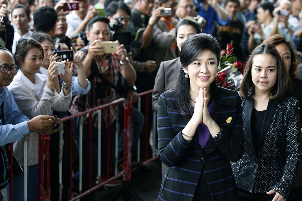 Former Thai prime minister Yingluck Shinawatra (second from right) performs the traditional Thai greeting as she arrives for the first hearing in her trial at the Supreme Court's Criminal Division for Holders of Political Positions, in Bangkok, Thai