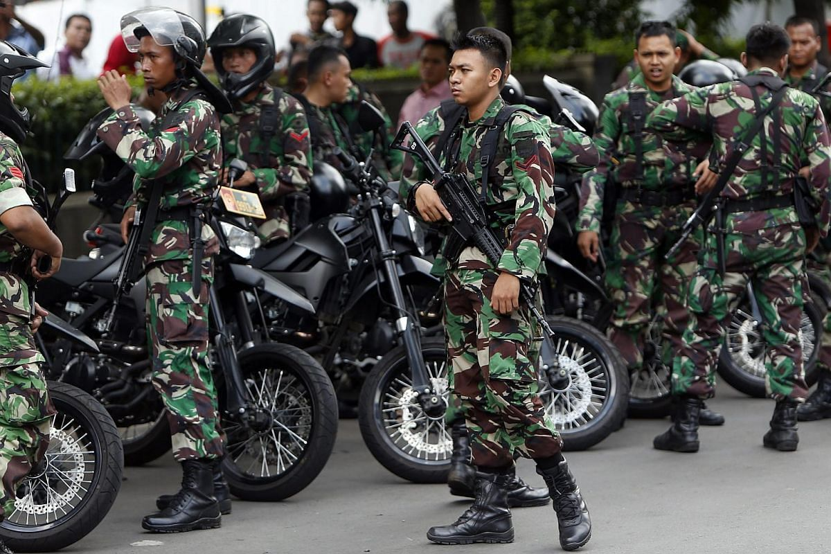 Armed Indonesian soldiers standing guard after gunfire and bomb blasts in front of a shopping mall in Jakarta.
