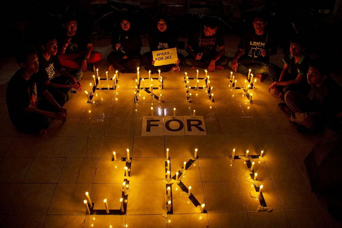 A group of Indonesian students holding placards during a candlelit protest in Surabaya, Eastern Java island, on Jan 14, 2016.