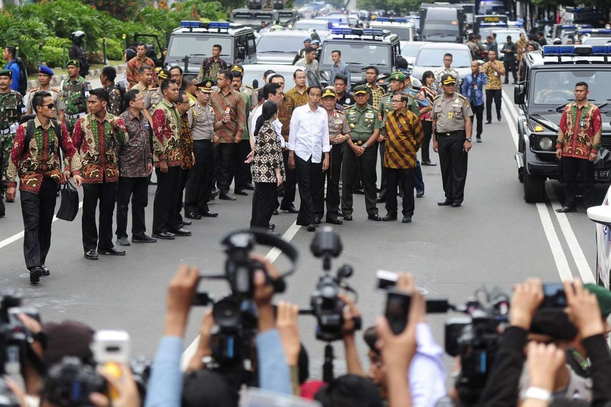 Indonesian president Joko Widodo (centre, white shirt) visiting the site of the bomb blast at Thamrin business district in Jakarta on Jan 14, 2016 .