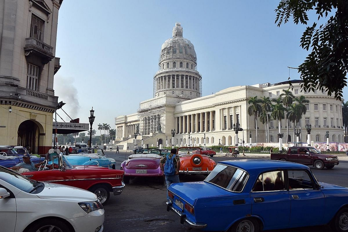 Nikki Muller with a street musician in Havana and the city's El Capitolio Building and vintage cars (above).