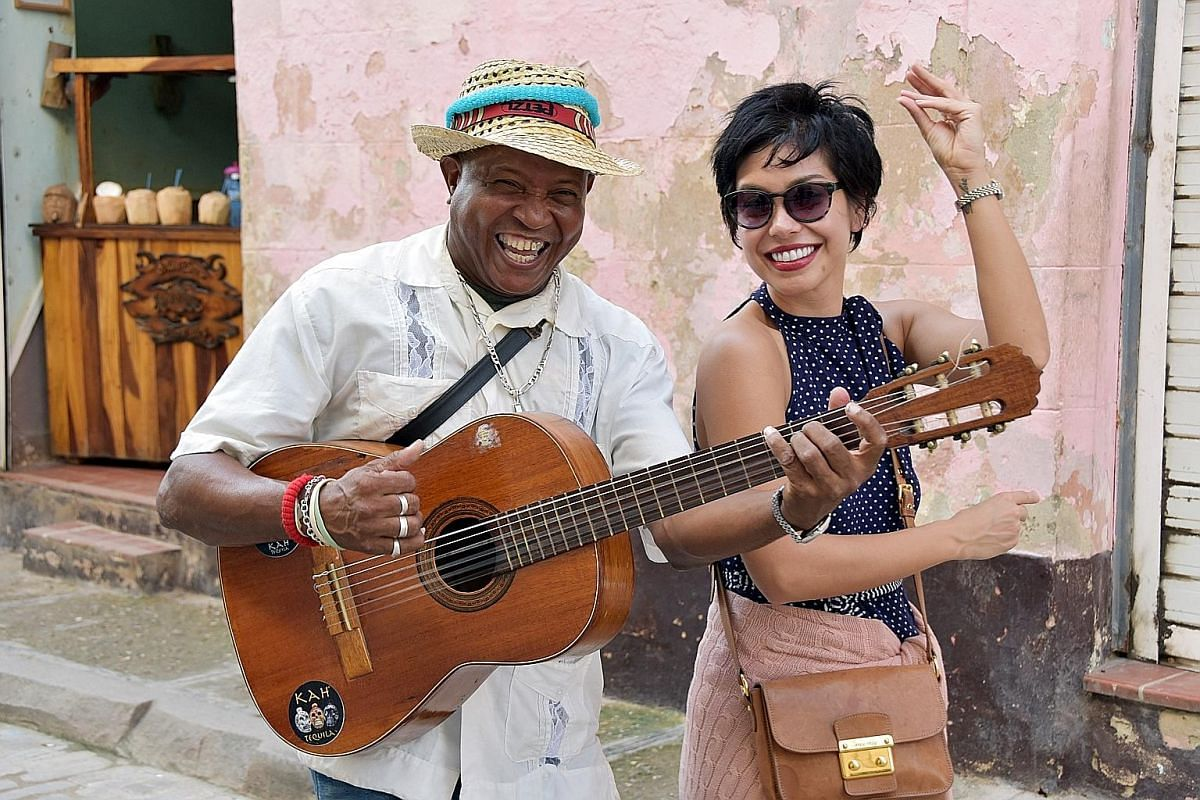 Nikki Muller with a street musician in Havana (above) and the city's El Capitolio Building and vintage cars.