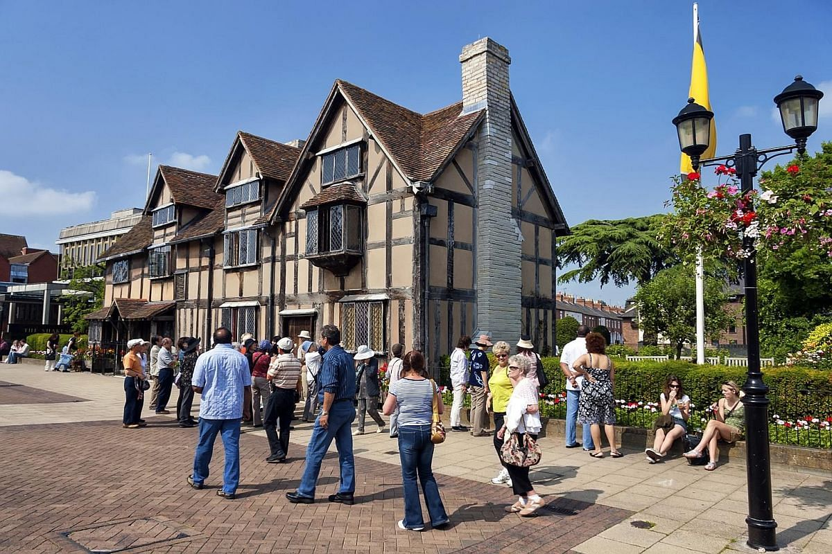 Tourists at Shakespeare's birthplace in Stratford-upon-Avon, England, a restored 16th-century half-timbered house.
