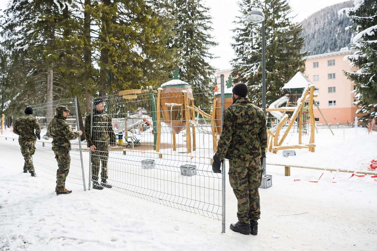 Swiss soldiers install the first security fences for the World Economic Forum, in Davos on Jan 7, 2016. This year Leonardo DiCaprio, Formula 1's Sebastian Vettel, Bill Gates, Bono, Greek Prime Minister Alexis Tsipras and Canada's Justin Trudeau, will