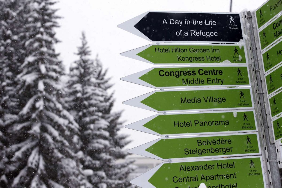 A signpost indicating various key locations for the World Economic Forum stands in Davos, Switzerland. Meetings at the four-day forum begin at 7 am and can end late into the night. And there are lots of meetings, held under varying degrees of secrecy