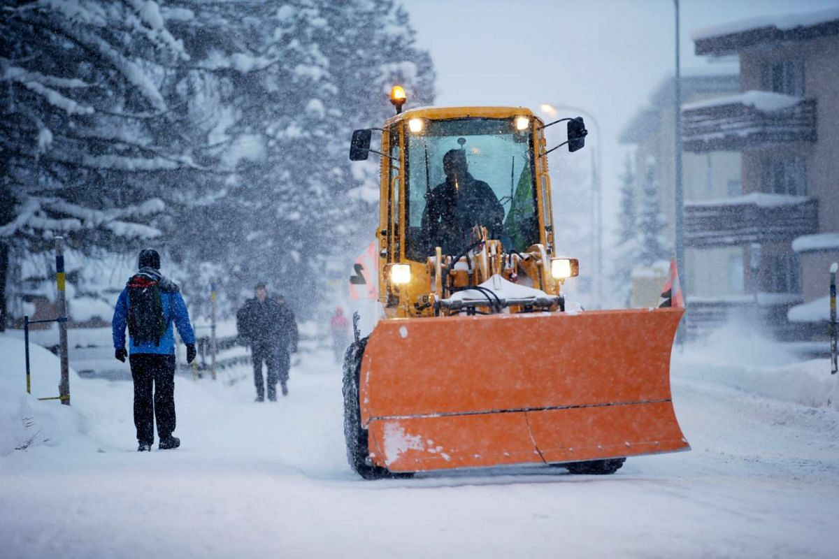 Pedestrians walk by as a worker drives a snow clearing tractor along the high street in Davos on Jan 16, 2016. Along with conversations, delegates also have a good time partying. There is also the option to go skiing. But few actually do.