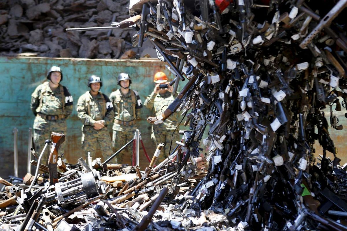 Confiscated weapons hang from a magnet before being destroyed at a foundry in Santiago, Chile, Jan 18, 2016. PHOTO: REUTERS
