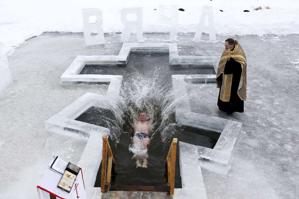 A man dips into the icy waters of a lake as part of celebrations for Orthodox Epiphany on the outskirts of Minsk, Jan 18, 2016. PHOTO: REUTERS