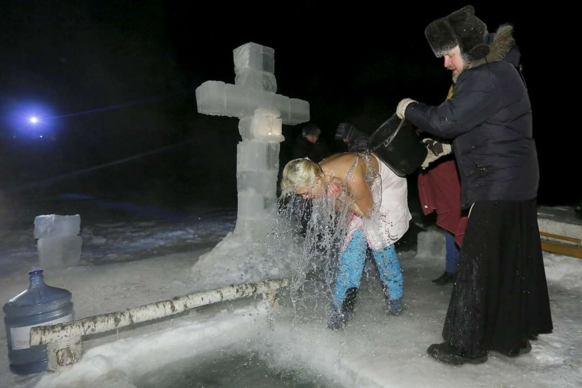 A priest pours icy water over a woman during the Orthodox Epiphany holiday on Jan 18, 2016.