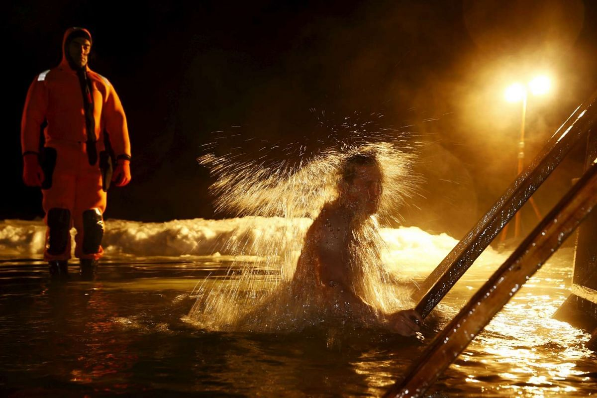 A man immerses himself in the icy waters of a lake during the Orthodox Epiphany holiday on Jan 18, 2016.