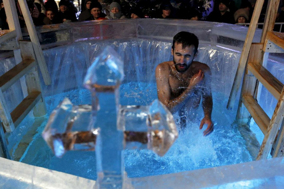 A man takes a dip in a font during the Orthodox Epiphany holiday on Jan 18, 2016.