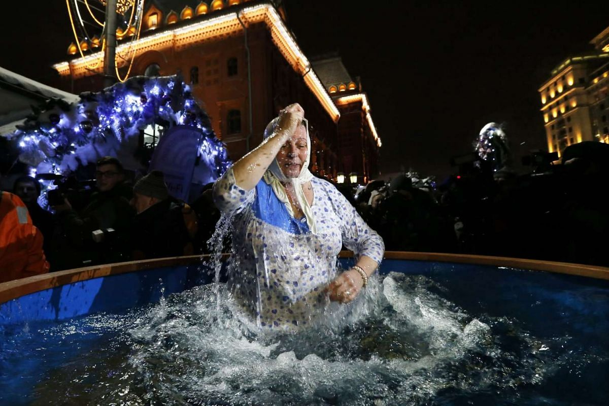 A woman takes a dip in a tub of ice water during the Orthodox Epiphany holiday on Jan 18, 2016.