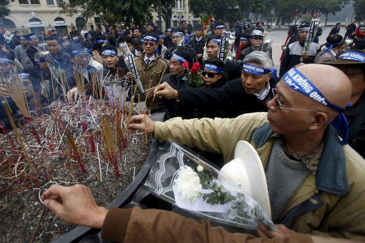 """Vietnamese activists with headbands that read """"People never forget"""" place incense during a gathering to commemorate the 42nd anniversary of China's occupation of the disputed Paracels in the South China Sea, in Hanoi, Jan 19, 2016. PHOTO: REUTERS"""