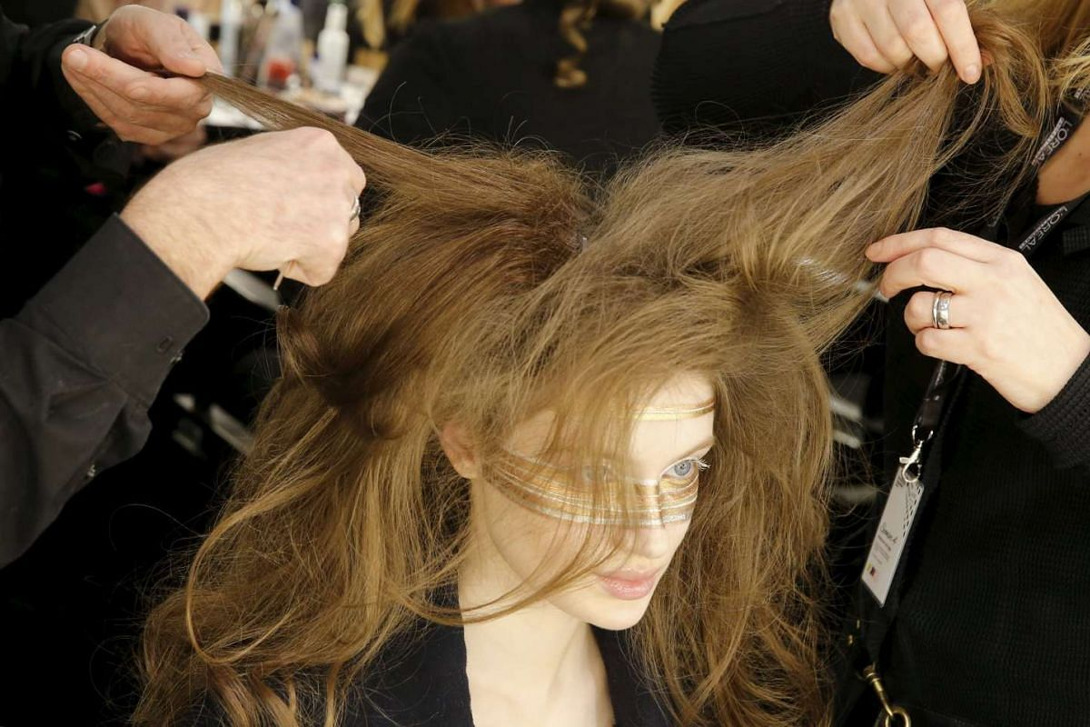 Models prepare backstage before presenting make-up creations during a show by Maybelline New York at the Berlin Fashion Week Autumn/Winter 2016 in Berlin, Germany, on Jan 18, 2016. PHOTO: REUTERS