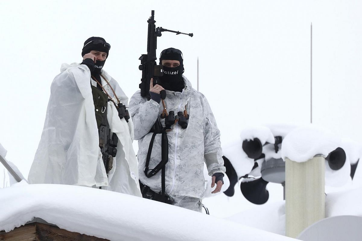 Armed members of the Swiss Police watch from the roof of the Hotel Davos ahead of the World Economic Forum (WEF) in Davos, Switzerland, on Jan 19, 2016.