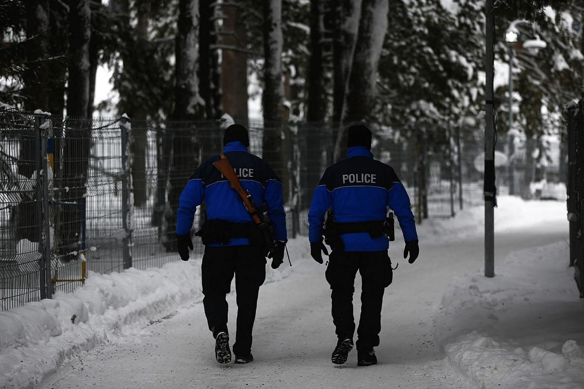 Armed members of the Swiss Police patrol the perimeter security fence outside the Congress Centre ahead of the World Economic Forum (WEF) in Davos, Switzerland, on Jan 19, 2016.