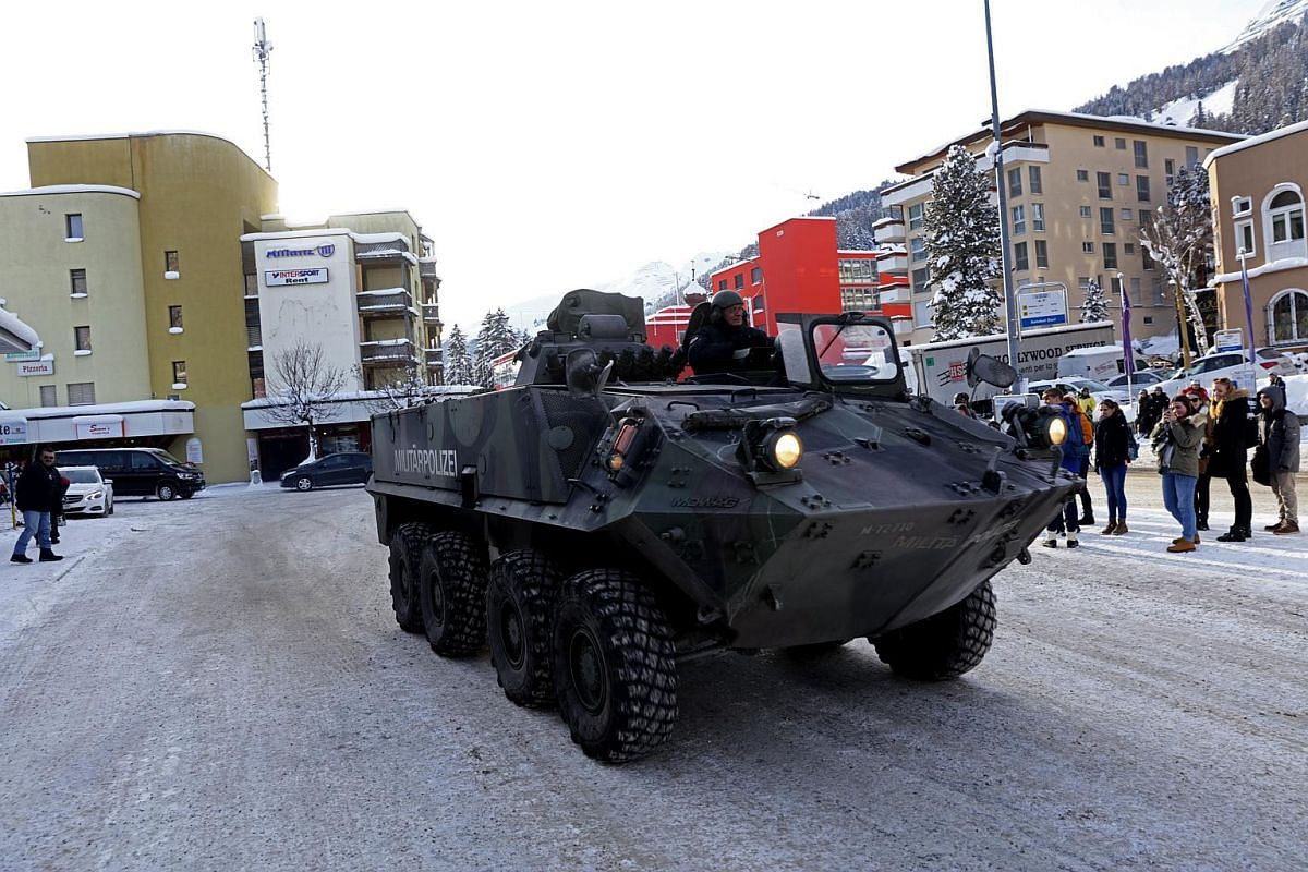 Pedestrian watch as an armoured Swiss military police vehicle drives past Davos Dorf railway station ahead of the World Economic Forum (WEF) in Davos, Switzerland, on Jan 18, 2016.