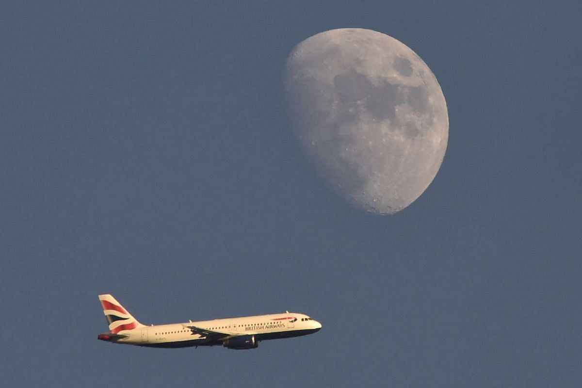 A British Airways passenger plane flies in the sky with the moon seen in the background, in London, Britain, Jan 19, 2016. PHOTO: REUTERS