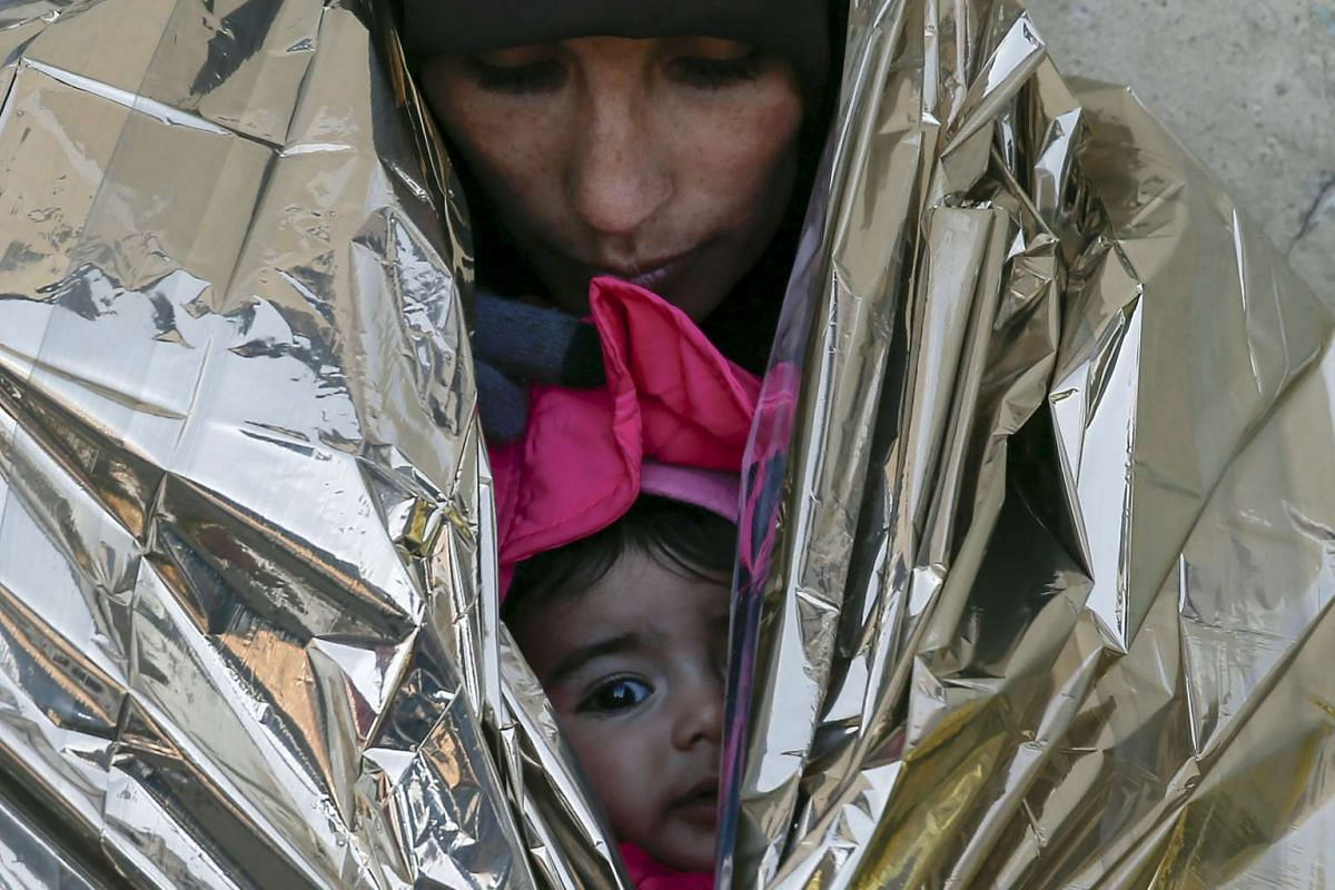 A migrant, wrapped with her child in a thermal blanket, waits for a train to Croatia, at a train station in Presevo, Serbia, Jan 20, 2016. PHOTO: REUTERS