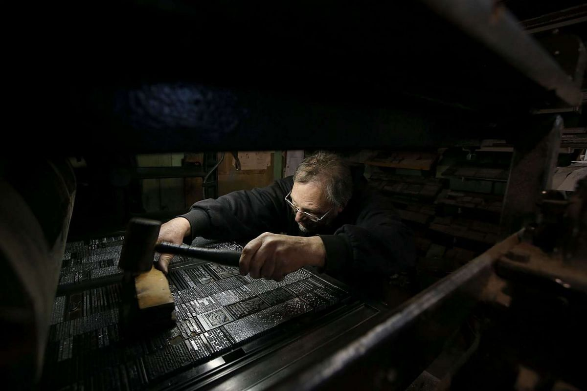 Saguache Crescent owner and editor Dean Coombs uses a mallet to even out a plate of metal type text before printing the Saguache Crescent newspaper using a Linotype on Jan 19, 2016, in Saguache, Colorado. PHOTO: GETTY IMAGES/AFP